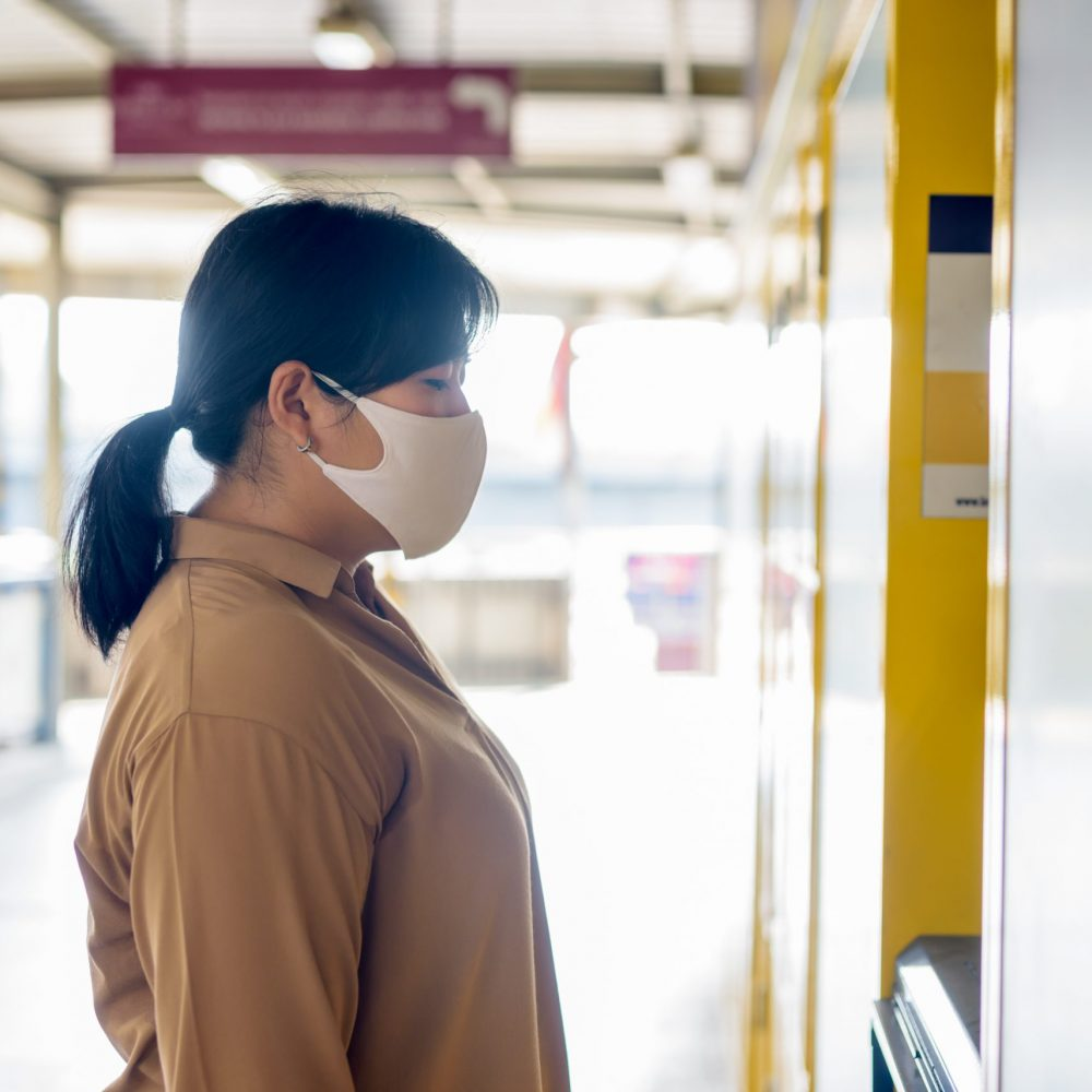 Portrait of overweight Asian woman with mask for protection from corona virus outbreak using self service locker box outdoors
